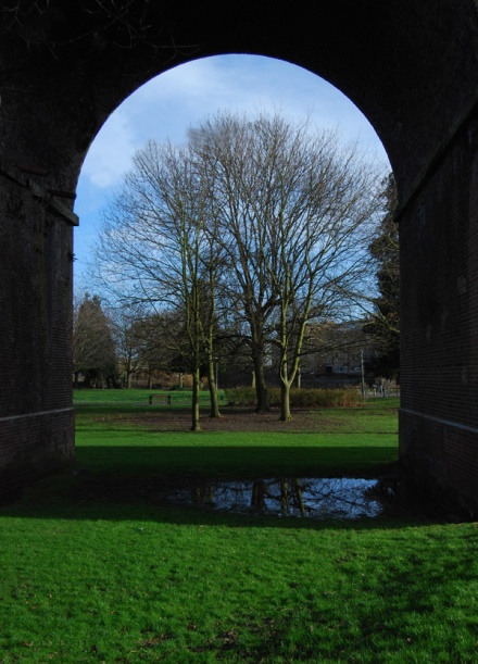 Photo of Central Park framed by the arch of a viaduct
